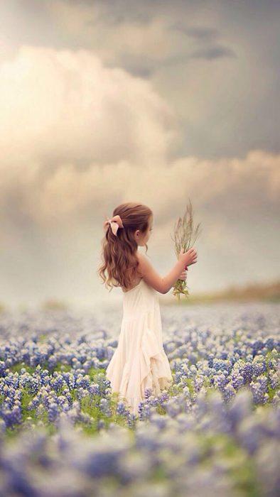 بنت صغار تمسك باقه من الورد في و سط حقل