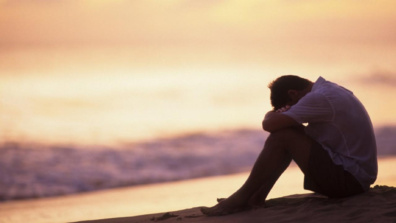رجل حزين يجلس وقت الغروب
