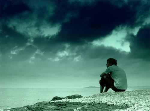 رجل يجلس بمفردة امام البحر